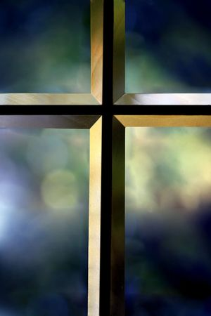 Bevelled glass cross with colorful blurred background Stock Photo
