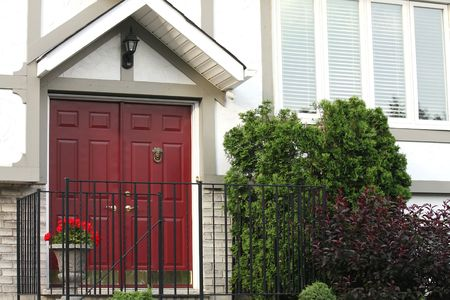 White brick house with red front door with brass knocker and summer bushes Stock Photo - 4536247