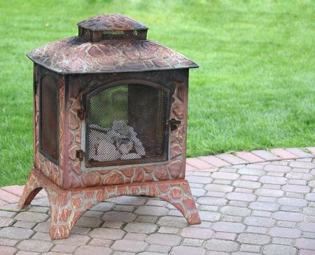Fireplace on backyard patio with green grass and copyspace Stock Photo