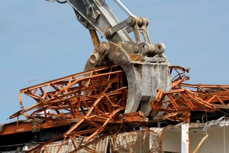demolition: Steel structure being demolished by heavy equipment