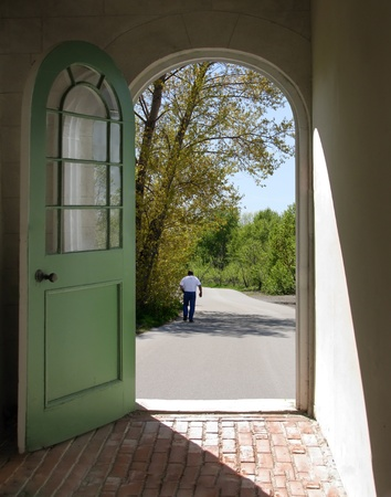 arched: Arched doorway with man walking away on path Stock Photo
