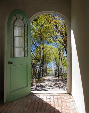 Łukowy otwarcie drzwi na drodze pokryte drzew wiosennych