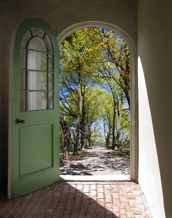 Arched doorway opening on path lined with spring trees Stock Photo