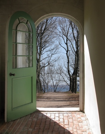 Arched doorway opening on winter path with bare trees