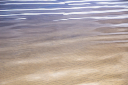 Warm rippled sand with softly rippled water Stock Photo