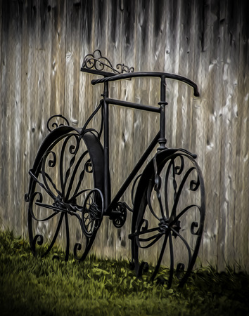 Vintage wrought iron bicycle leaning on wooden fence