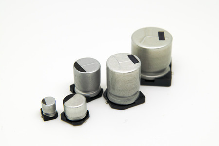 electrolytic: Different size aluminum electrolytic capacitors in white background.