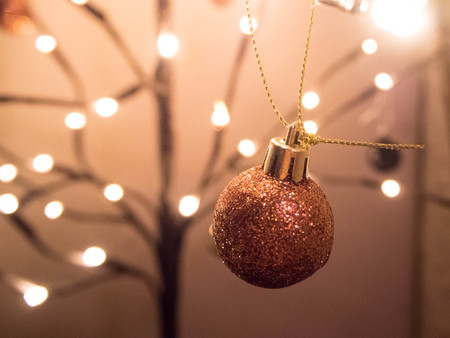 Close up rose gold glitter bauble hanging on decorated leafless tree, Christmas decoration Stock Photo