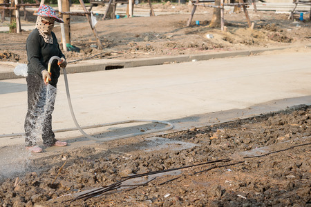 puttering: labor women watering  in construction site