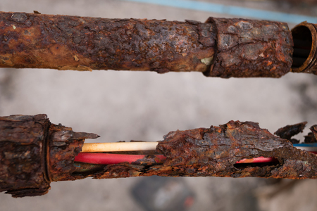 corrosion: Fragments of old  pipes ,metal pipe destroyed. Rusty steel tube with holes metal
