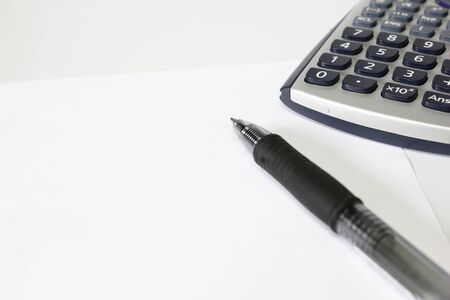 Calculator, pen and paper on white background