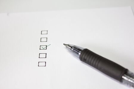 Checklist with green tick mark and ball pen