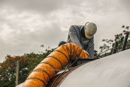 Worker blow fresh air into vessel
