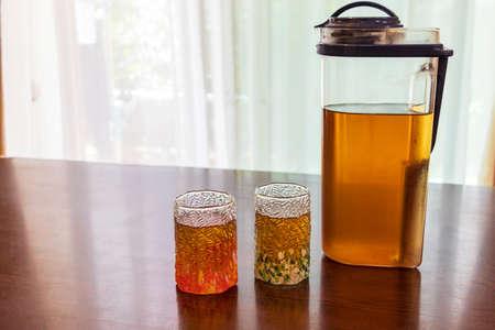 a glass of barley tea and a plastic pot Banco de Imagens