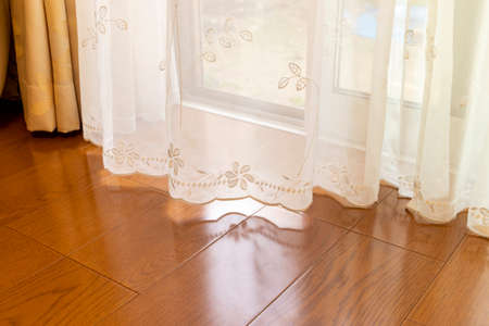 Wood flooring and lace fabric curtain