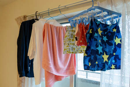 Hanging laundry on the curtain rail in the room