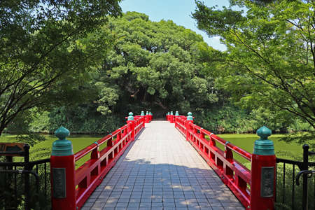 Red bridge crossing the pond to the green hill in Tennoji Park