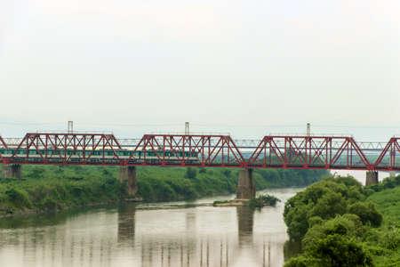 Red railway bridge over Kizu River in Yawata, Kyoto