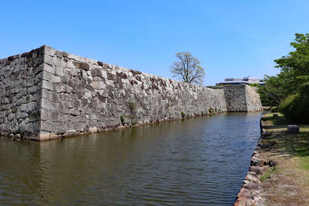 Stone wall and moat left in Japanese castle ruins
