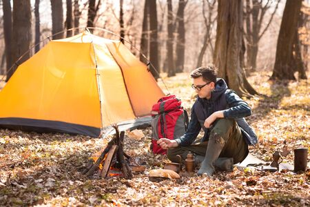 A young traveler in the forest is resting near the tent and cooked breakfast in nature.