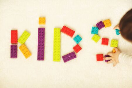 Close up of child's hands playing with colorful plastic bricks. Kid have fun and play with constructor bricks. Development toys.