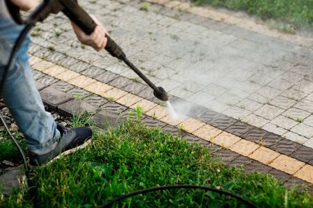 Close up photo of a man hands, cleans a tile of grass in his yard. High pressure cleaning.