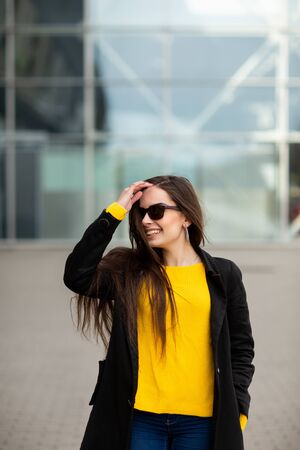 Portrait of a beautiful fashionable stylish woman in bright yellow sweater. Street style shooting.