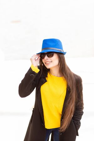 Portrait of a beautiful fashionable stylish woman in bright yellow sweater and blue hat. Street style shooting.