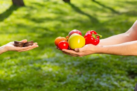 Female and male hands, holding and comparing cookie vs vegetables and fruits. Background of the green park. Stock Photo
