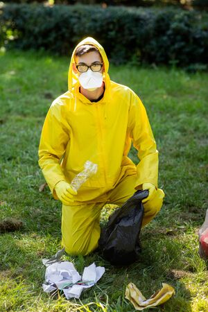 Portrait of a man in a yellow protective suit and mask. The man sat down and collected the garbage in a trash bag. Garbage collection in the park. Imagens