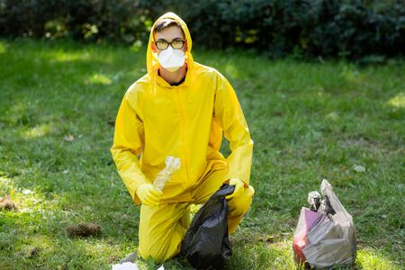 Portrait of a man in a yellow protective suit and mask. The man sat down and collected the garbage in a trash bag. Garbage collection in the park. Stock Photo