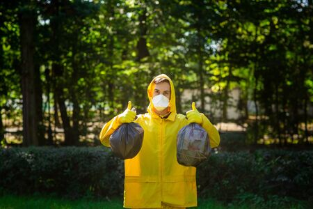 A man in a yellow protective suit and mask holds bags of garbage and shows class with his hands. Garbage collection in the park. Stock Photo