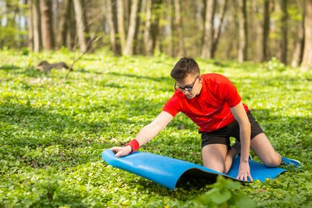 Man in red tshirt, spreads a blue yoga mat in a park on green grass for exercises and relaxation. Healthy lifestyle.