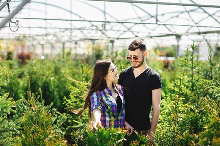 Young couple, man and woman, standing together in the garden center and choose plants for greening the house. Gardening and planting concept. Shopping.