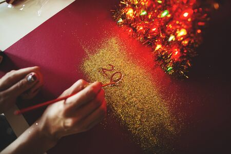 The woman's hand paint the figure of 2020 in the claret background with sparkles. New Year's concept.
