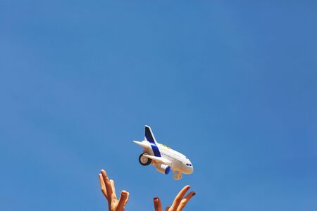 Woman's hands throws in the air a white and blue children's airplane. Dreams of traveling during a coronavirus quarantine. Blue sky background. Copy space.