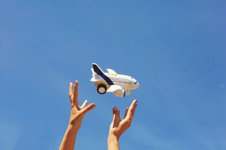 Women's hands throw white and blue children's airplane. Blue sky background.