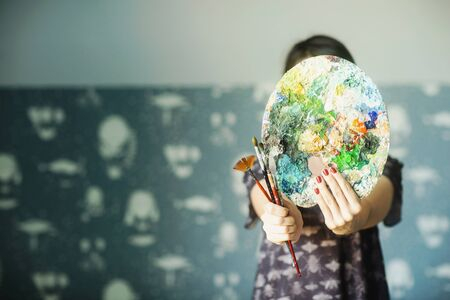 A woman holds a palette of oil paints and brushes in front of her. Art concept.