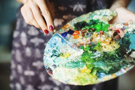 Woman's hands holding paintbrush and palette with oil paints. Close up. Art concept. Standard-Bild