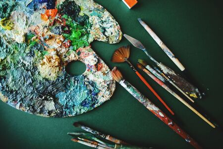 Palette with colors, paints and brushes on a green background. Painter workplace. Standard-Bild