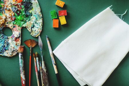 Palette with colors paints, brushes and the canvas on a green background. Painter workplace. Space for text