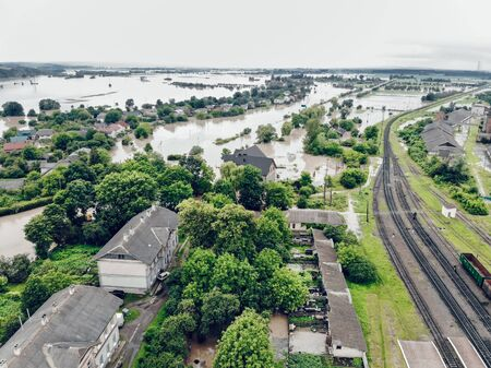 View of the railway track and the flooded city. Natural disaster in Ukraine. Roads, streets and houses are flooded with dirty water.