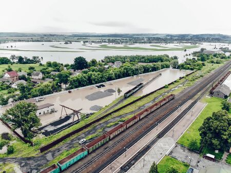 View of the railway track and the flooded village. Natural disaster in Ukraine. Roads, streets and houses are flooded with dirty water.