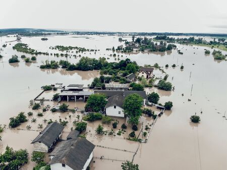 Flooded village on Ukraine. Natural disaster in Halych, courtyards and streets in dirty yellow water. Global catastrophe, climate change, flood concept.
