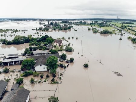 Aerial view of the flooded village of Halych, Prykarpattia, Western Ukraine. The flood on the Dniester River caused a natural disaster. Streets, roads, parks and houses in dirty rainwater.