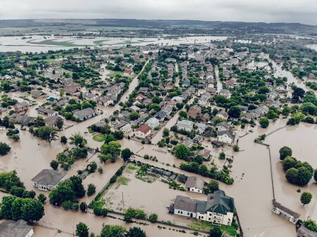 Flooded village on Ukraine. Natural disaster in village Halych, courtyards and streets in dirty water. Global catastrophe, climate change, flood concept.