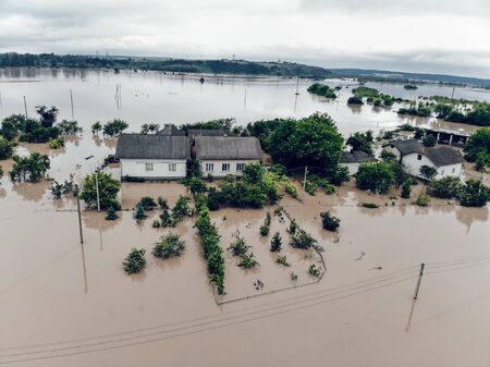Flooded village on Ukraine. Natural disaster in Halych. Street with trees and houses in dirty river water. Global catastrophe, climate change, disasters concept.