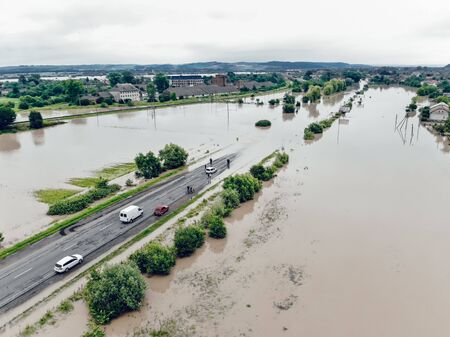 Cars and people cannot cross a flooded road. Aerial view of the flooded road, streets and houses in the city. Global catastrophe, climate change, flood concept.