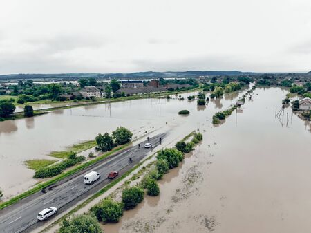 Cars and people cannot cross a flooded road. Aerial view of the flooded road, streets and houses in the village. Global catastrophe, climate change, flood concept.