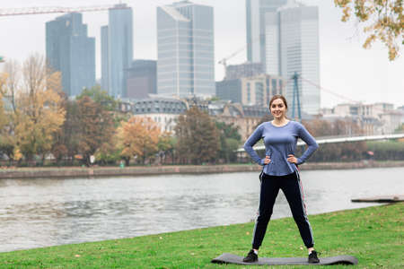 Sporty young woman in sportswear doing stretching exercises on the yoga mat near the river. Behind the panorama of the big city. Active lifestyle.